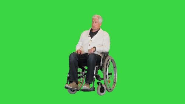 Alter Mann sitzt allein im Rollstuhl und wartet auf einem Green Screen, Chroma Key.