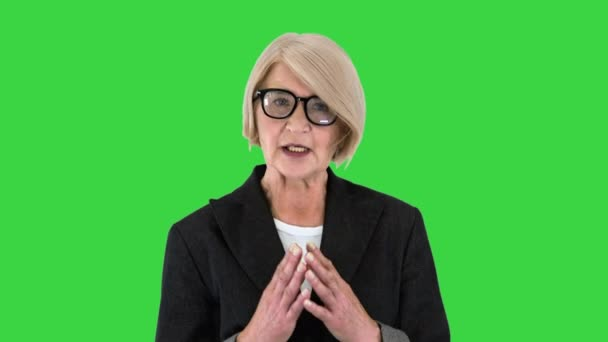 Senior-Unternehmerin Führungslehrerin schaut in die Kamera sprechen auf einem Green Screen, Chroma Key.