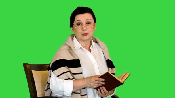 Seniorin liest ein Buch laut vor der Kamera auf einem Green Screen, Chroma Key.