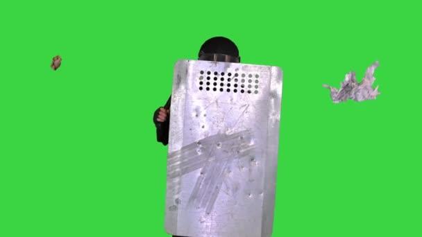 Müll wird in den Bereitschaftspolizisten geworfen, mit einem Schild auf einem Green Screen, Chroma Key.