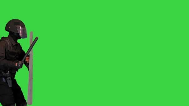 Bereitschaftspolizist mit Schutzschild und Gummiknüppel auf einem Green Screen, Chroma Key.