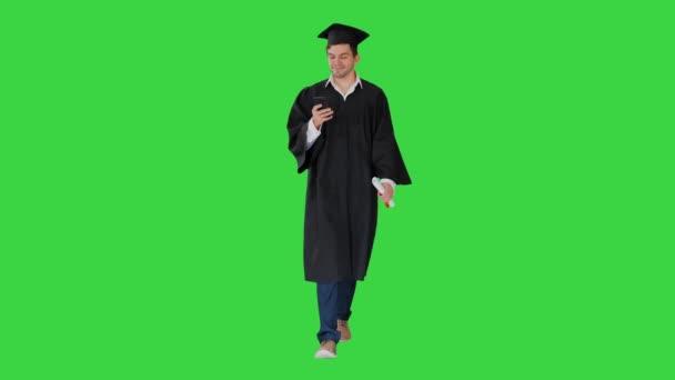 Muž student v maturitní šaty zkontrolovat svůj telefon při chůzi na zelené obrazovce, Chroma Key.