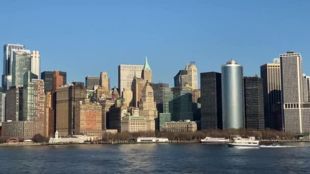 V centru Manhattanu za slunečného dne, Battery Park, rušný přístav, projíždějící trajekty