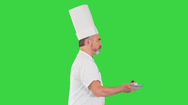 Muž pečivo kuchař chodí rychle s dezertem v rukou na zelené obrazovce, Chroma Key.
