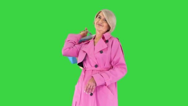 Schöne Seniorin im Trenchcoat mit Einkaufstaschen auf einem Green Screen, Chroma Key.