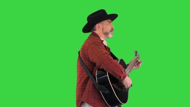 Muž v kovbojském klobouku kráčející a hrající na kytaru na zelené obrazovce, Chroma Key.