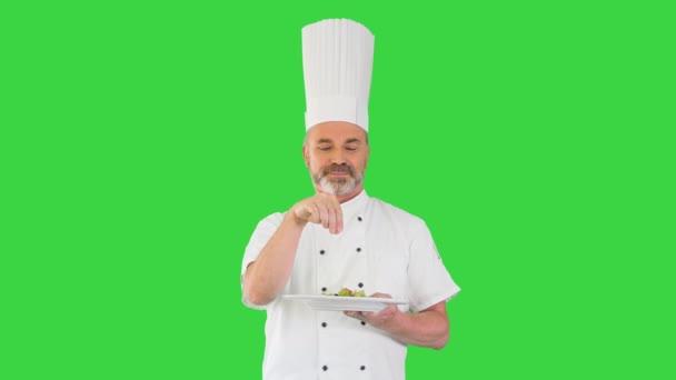 Séf díszíti a salátát, és nézi a kamera mosolyog a zöld képernyőn, Chroma Key.