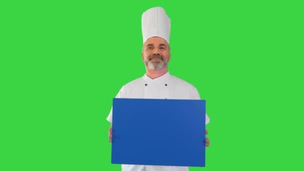 Mosolygó férfi szakács szakács tartja üres fórumon a zöld képernyőn, Chroma Key.