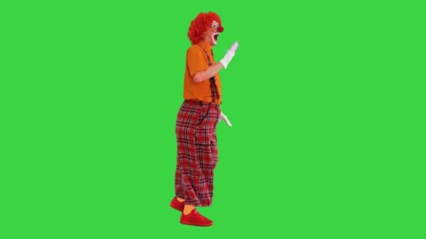 Bohóc vörös parókában, aki mindenkit üdvözöl a Zöld vásznon, Chroma Key..