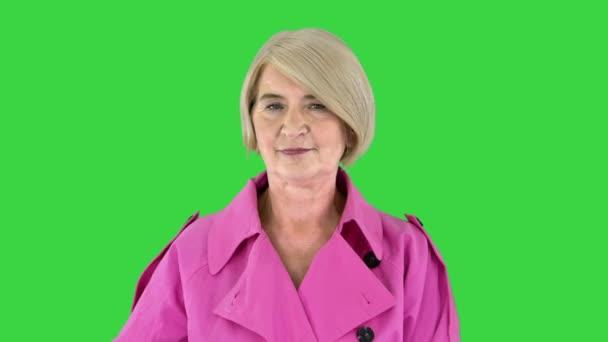 Schöne stylische Seniorin im Trenchcoat posiert auf einem Green Screen, Chroma Key, vor der Kamera.