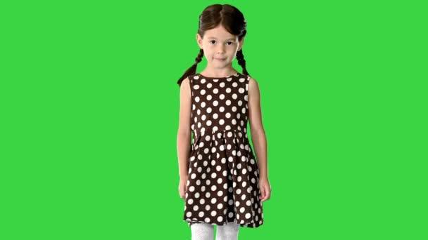 Dívka v puntíkovaných šatech s prasečími ocasy kráčející a stydlivě se usmívající do kamery na zelené obrazovce, Chroma Key.