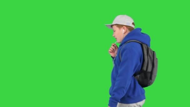 Módní dospívající chlapec mluví na mobilním telefonu s rukama volnýma, zatímco jde kolem a říká někomu cestu na zelené obrazovce, Chroma Key.