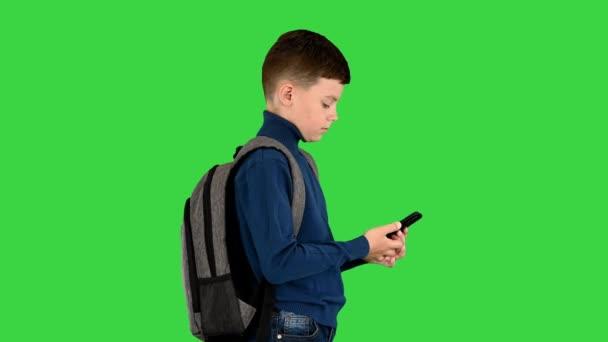 Školák s batohem pomocí mobilního telefonu na zelené obrazovce, Chroma Key.