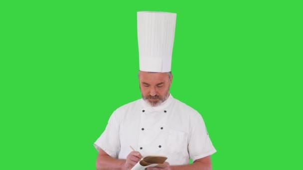 Starší kuchař si dělá poznámky na zelené obrazovce, Chroma Key.