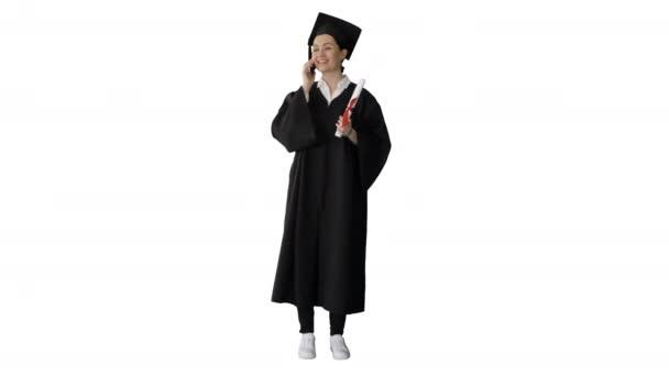 Emotionale Studentin im Abschlussgewand telefoniert mit Diplom auf weißem Hintergrund.