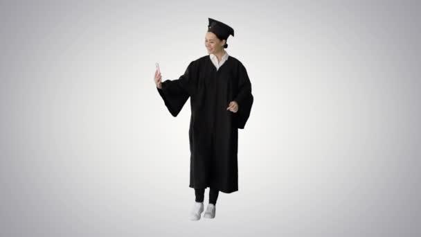 Šťastná žena absolvent v minometu dělat selfie na telefonu na gradient pozadí.