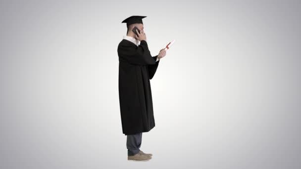 Šťastný absolvent mladý muž v čepici a šaty mluvit s rodičem na mobilním telefonu na gradient pozadí.