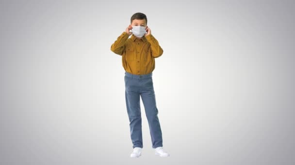 Little boy taking his face mask off and smiling at camera on gradient background.