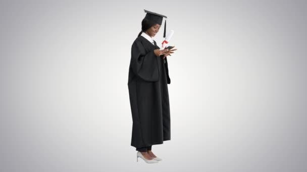 Happy African American žena absolvent držení diplomu a textové zprávy na telefonu na gradient pozadí.