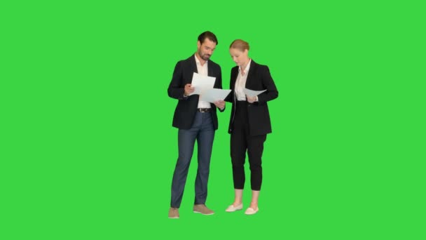 Two young business people talking about documents on a Green Screen, Chroma Key.