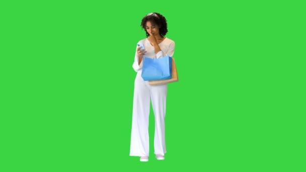 Glückliches afroamerikanisches Mädchen trägt Käufer und sucht am Telefon auf einem Green Screen, Chroma Key.