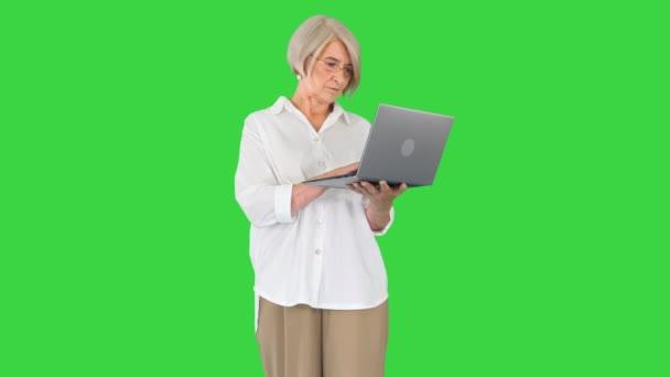 Grey vlasy spokojené dospělé ženy pomocí notebooku stojící na zelené obrazovce, Chroma Key.