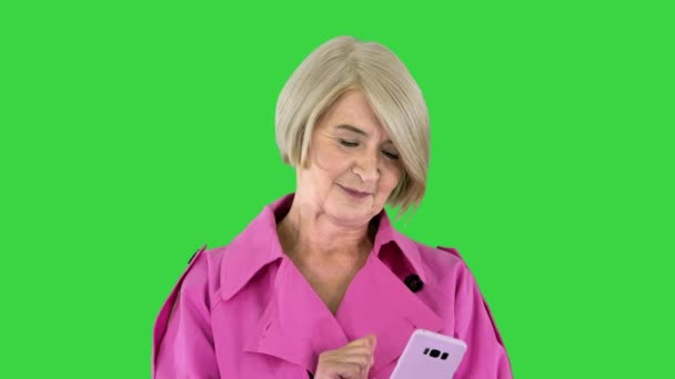 Fröhliche Seniorin im pinkfarbenen Trenchcoat mit ihrem Smartphone auf einem Green Screen, Chroma Key.