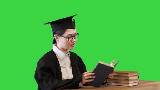 Absolvent v brýlích čtení knihy sedí za stolem na zelené obrazovce, Chroma Key.