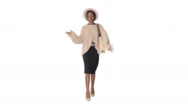 Stilvolle afrikanisch-amerikanische Frau in Strickwaren und weißem Hut tanzt beim Gehen auf weißem Hintergrund.