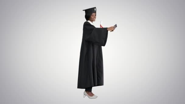 Boldog afro-amerikai női diplomás birtokában diploma és szelfi gradiens háttér.