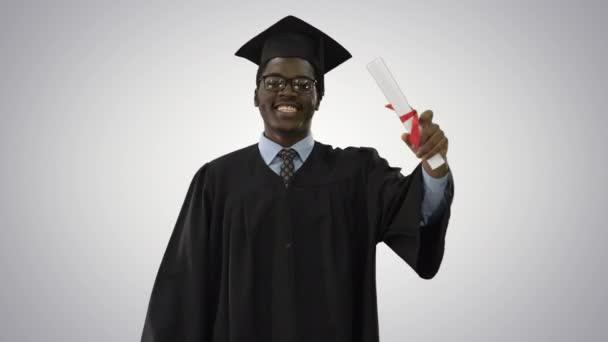 Boldog afro-amerikai férfi diák ballagási köntösben séta diplomával és beszél a kamera gradiens háttér.