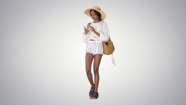 Smiling young african american woman in a straw hat texting on her phone on gradient background.