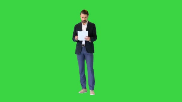 Young business man looking through the documents on a Green Screen, Chroma Key.