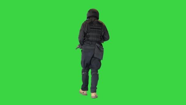 Spec ops Polizist SWAT mit einem Gewehr zu Fuß auf einem Green Screen, Chroma Key.