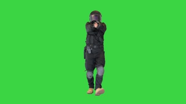 Swat Agent läuft und zielt mit einer Waffe auf einem Green Screen, Chroma Key.