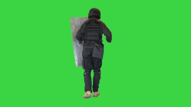 Bereitschaftspolizist läuft mit Schild und Schlagstock auf einem Green Screen, Chroma Key.