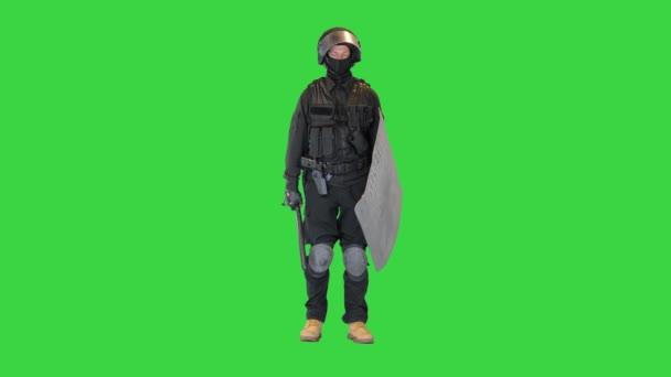 Spezialeinheit Bereitschaftspolizist mit Schild und Schlagstock, der auf einem Green Screen wartet, Chroma Key.