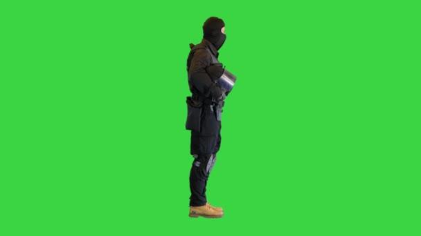 Bereitschaftspolizist mit Helm in der Hand auf einem Green Screen, Chroma Key.