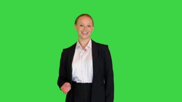 Junge Geschäftsfrau begrüßt und erklärt etwas, das vor laufender Kamera auf einem Green Screen, Chroma Key, gesprochen wird.