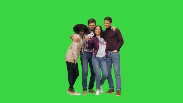 Four friends, two girls and two boys, taking a selfie, posing, smiling, looking at the camera on a Green Screen, Chroma Key.