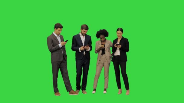 Mladí studenti v oficiálních šatech absorbované s jejich smartphony na zelené obrazovce, Chroma Key.