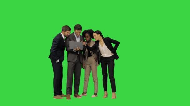 Takım elbiseli genç meslektaşlar yeşil ekran Chroma Key 'de dizüstü bilgisayara bakan bir projeyi tartışıyorlar..