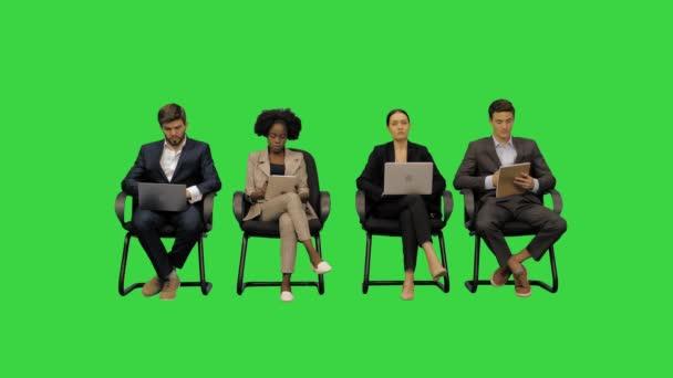 Podnikatelé na konferenci poslouchají a zapisují si poznámky na svém notebooku na zelené obrazovce, Chroma Key.