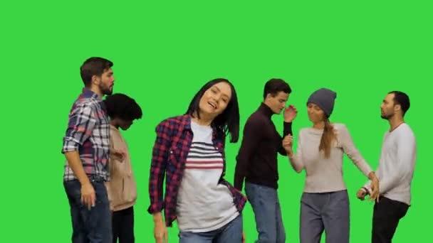 Partide sıradan kıyafetlerle dans eden ve kameraya bakan genç ve güzel bir kız, yeşil ekranda dans eden diğer insanlar, Chroma Key.