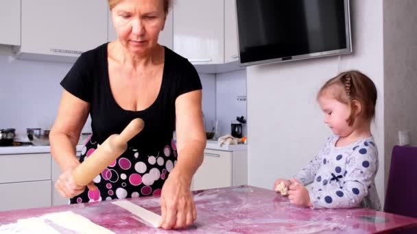Grandma helps her daughter roll the dough in the kitchen to bake cookies. Grandma and daughter bake pizza together in the kitchen. The girl helps her mother roll out the dough with a rolling pin.