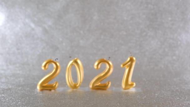zlaté silvestrovské svíčky 2021 na stříbrném pozadí. moderní koncept. rozmazat abstraktní pozadí