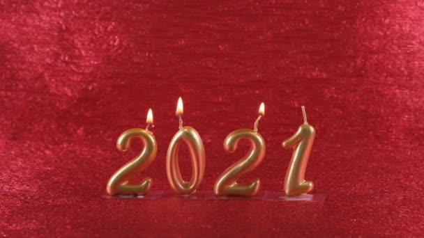 samice ruka světla zlatý Nový rok svíčky 2021 na červeném pozadí.