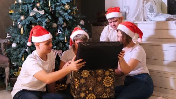 A család ajándékot cserél a karácsonyfa előtt.