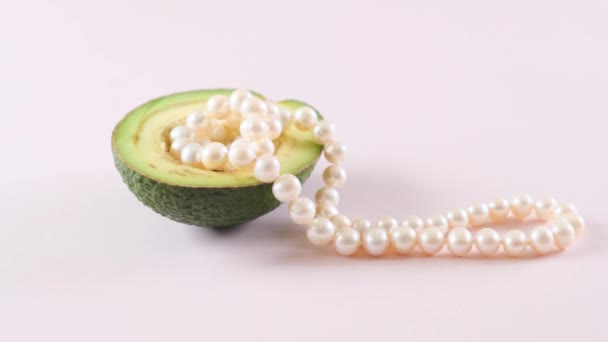 half an avocado with pearls on a light pink background. surrealism. Fashionable food design.
