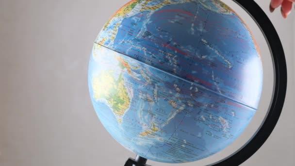 Model globusu se otáčí na dřevěném stole. Bílá stěna prázdné místo pozadí